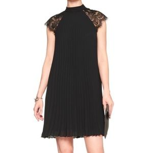 Pleated black swing dress with lace cap sleeves